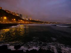 Sunset in Lima, Peru (` Toshio ') Tags: toshio lima peru southamerica miraflores miraflorescliffs cliffs pacificocean pacific ocean beach water waves evening sunset city clouds fujixt2 xt2 surf jetty