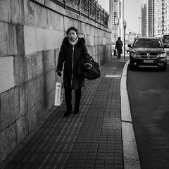 Lady bags (Go-tea 郭天) Tags: qingdao shandong républiquepopulairedechine old lady woman alone lonely walk walking sidewalk bags portrait pavement lines cold winter sun sunny shadow cars wall scarf gloves street urban city outside outdoor people candid bw bnw black white blackwhite blackandwhite monochrome naturallight natural light asia asian china chinese canon eos 100d 24mm prime