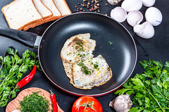 Fried chicken eggs with greens in a frying pan (wuestenigel) Tags: egg natural garlic pepper table chili background hot chicken delicious cook cooked meal traditional view eating closeup cooking breakfast healthy eggs food white ingredient bread pan top fried black green fresh fryingpan tomatoes kitchen