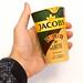 Hand hält die geschlossene Verpackung des Latte Kaffees von Jacobs Krönung mit Baileys aus 100% Arabicabohnen und Alpenmilch