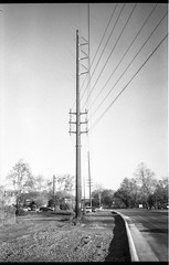 Powerlines, roadway, new curbing, near sunset, Asheville, NC, Olympus XA, Ilford FP4+, HC-110 developer, 4.22.19 (steve aimone) Tags: powerlines roadway curbing latelight riverdistrict asheville northcarolina olympusxa ilfordfp4 hc110developer compactcamera 35mm 35mmfilm film monochrome monochromatic blackandwhite rangefinder urbandecay urbanlandscape