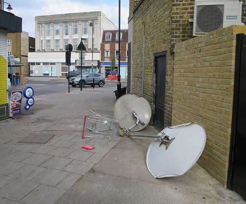 Satellite dishes and broken supermarket trolley dumped in alley St Loy's Road