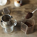 scooping coffee into metal filter, for Vietnamese coffee