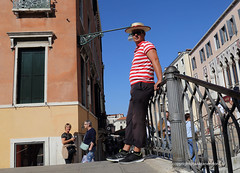 Gondolier (Jan Kranendonk) Tags: venice italy italian venetian europe european man gondolier bridge traditional custom people tourism tourists buildings houses sunny hat sunglasses sky blue railing city tradition culture historical striped red white