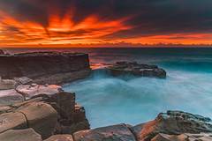 A Vibrant Flaming Sunrise Seascape (Merrillie) Tags: daybreak sunrise northavoca nature water nsw centralcoast overcast rocky sea newsouthwales waves earlymorning morning rocks landscape ocean cloudy waterscape avocabeach coastal dawn outdoors seascape australia coast northavocabeach sky