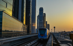 A metro train running on track at sunset (phuong.sg@gmail.com) Tags: arab arabia architecture building center city cityscape design development downtown dubai east editorial emirates futuristic industry landmark landscape metro middle modern motion new rail railroad railway road skyline skyscrapers station street subway sunset terminal tourism tower traffic train transport travel uae united urban