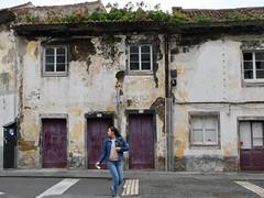 Looking back (halifaxlight) Tags: portugal saomiguel ribeiragrande urban downtown street buildings neglect decay woman walking windows doors purple stucco terracotta plants
