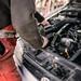 Automehaniker arbeitet am Motor eines Wagens