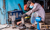 2019 - Cambodia - Sihanoukville - Tumnuk Rolok (Ted's photos - For Me & You) Tags: 2019 cambodia cropped nikon nikond750 nikonfx tedmcgrath tedsphotos vignetting welder worker workinghardforaliving goggles welding industrial streetscene street fan sato satowelder inverterarcwelder sandals sparks mask facemask 1people people male man ក្រុងព្រះសីហនុ sihanoukville