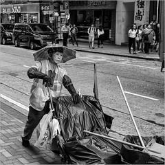 Sun protected street cleaner in Hong Kong (John Riper) Tags: johnriper street photography straatfotografie square vierkant bw black white zwartwit mono monochrome candid john riper xt3 fujifilm hong kong cleaner sweeper lady umbrella parasol