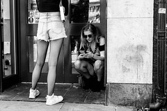 Fishnets (Silver Machine) Tags: oxford oxfordshire streetphotography street candid girls standing crouching fishnets fishnettights trainers phone sunglasses shorts denim doorway fujifilm fujifilmxt10 fujinonxf35mmf2rwr blackwhite bw mono monochrome
