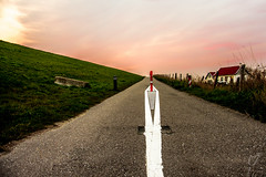 """""""Dutchland"""" Dikes and beautiful skies (wardkeijzer_107) Tags: vanishingpoint point view redsky orange road asphalt holland netherlands infrastructure lines cycleroad skyporn green dyke"""