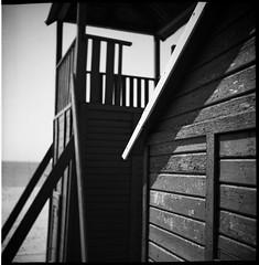 Finding Perspectives pt.II (Manuel&TheSea) Tags: monochrome mediumformat medium format filmphotography ishootfilm tlr analoguephotography analogue bw iso50 ilfordfilm film ilford panf50 panf ilfordpanf50 somberthiotparis luxoflex atos2 6x6 squareformat 120film vintagecamera vintage 50scamera 50s 50stlr twinlensreflex beach cabin lifeguardtower