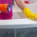 Hand in yellow protective glove cleaning bathtub