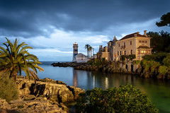 The Farol de Santa Marta and the Casa de Santa Maria - Cascais, Portugal (Bela Lindtner) Tags: cascais lisboaregion portugal belalindtner lindtnerbéla nikon d7100 nikond7100 nikkor 18105 nikkor18105 nikon18105 portugália bluesky sky clouds buildings building architecture thefaroldesantamarta tree sea atlanticocean atlantióceán atlanticsea rocks water outdoor outside bluehour thebluehour