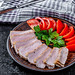 Sliced baked meat with fresh tomatoes and parsley