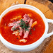 Solyanka soup with smoked meat in tureen close-up