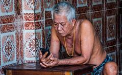 2019 - Cambodia - Sihanoukville - Tumnuk Rolok (Ted's photos - Returns late November) Tags: 2019 cambodia cropped nikon nikond750 nikonfx tedmcgrath tedsphotos vignetting old oldman cellphone grey greyhair goldchain shirtless table sihanoukville tumnukroloksihanoukville tumnukrolokcambodia sihanoukvillecambodia male man 1people ក្រុងព្រះសីហនុ