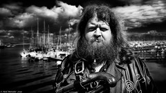 Big Dave. (Neil. Moralee) Tags: brixhampiratesneilmoralee neilmoralee man face portrait beard hair pirate black white mono monochrome bw blackandwhite street brixham devon uk gun clouds sky sail sailor sea ocean captain sunshine