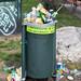 Überfüllte Mülltonne mit Abfall drumherum