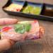 Hand hält eine Sommerrolle gefüllt mit Avocado, Mango, Paprika, Rotkohl, Karotten und Reisnudeln mit verschiedenen Saucen im Hintergrund