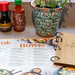 Soy sauce, hot chili sauce, mint and the menu of the coa Wok & Bowl restaurant with wooden design