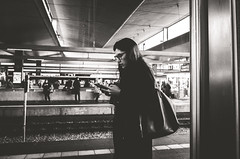 Waiting and Typing and Looking Cool (Diggoar) Tags: train trainstation handy smartphone waiting blackandwhite bw ricohgr 28mm wideangleportrait street streetphotography streetscene city