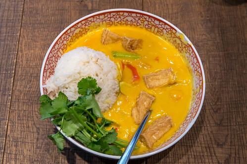 Ansicht von oben auf gelbes veganes Tofu-Cocos-Curry, Paprika, Champignons, Süßkartoffeln, Babyspinat, Blumenkohl, Bohnen und Jasmin-Duftreis