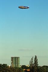 Berlin Luftschiff über dem Kreisel Steglitz 2001 (rieblinga) Tags: berlin steglitz kreisel hochhaus 2001 luftschiff zeppelin werbung deutsche vermögensberatung analog canon eos 1v agfa ct precisa 100 diafilm flug e6