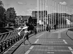 Throw her into the Taff (Nikonsnapper) Tags: olympus omd m45 zuiko 45mm street bw boardwalk cardiff principalitystadium couple fun