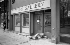 Treason Gallery (sailronin) Tags: seattle washington pioneersquare treasongallery streetphotography blackandwhite man sleeping blanket woman sidewalk door artgallery building analog film ilfordfp4 rodinal