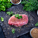Fresh raw steak with spices and herbs on a black stone background