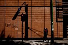 """(untitled)"" - Milano 2019 (Andrea Comino 22:20) Tags: couple shadows sunnyday sun unposed candid citylife city streetphotographer streetphotography urban street arrows blue red green color italia italy milan milano"