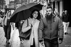 Hand In Hand (Cycling-Road-Hog) Tags: beard blackwhite candid canoneos750d citylife colour efs55250mmf456isstm edinburgh edinburghstreetphotography monochrome people places princesstreet scotland street streetphotography streetportrait style umbrella urban