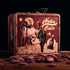 Caps And A Lunchbox (tommycochranephotography) Tags: fallout universe metal lunch box nuka cola soft drink rust aged damaged emblem logo text caps tin wood vintage black handle women gun stars