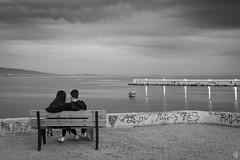 Silent movie (tzevang.com) Tags: sea seascape couple boys greece piraeus bench enjoy bw bythesea beach afternoon view fujifilm x100f