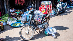 2019 - Cambodia - Sihanoukville - Phsar Leu Market - 16 of 25 (Ted's photos - Returns late November) Tags: 2019 cambodia cropped nikon nikond750 nikonfx tedmcgrath tedsphotos vignetting motorcycle beer beercans cambodiabeer shadow market sausages honda hondadream vegetables cans phsarleumarket phsarleumarketsihanoukville sihanoukvillecambodia sihanoukville streetscene street