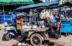 2019 - Cambodia - Sihanoukville - Phsar Leu Market  - 17 of 25 (Ted's photos - Returns late November) Tags: 2019 cambodia cropped nikon nikond750 nikonfx tedmcgrath tedsphotos vignetting motorcycle streetscene street canopy cart foodcart wheel phsarleumarket phsarleumarketsihanoukville sihanoukville sihanoukvillecambodia uppermarket sihanoukvilleuppermarket umbrella shadow sandals
