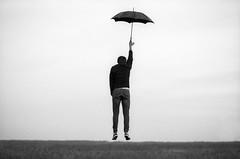 Blown by the Wind (Dmitriy Ryabov) Tags: canoneos1v canon1v canon dmitriyryabov canonef85mmf12liiusm bw monochrome blackandwhite photo photography portrait film people man umbrella fly levitation analogeffects