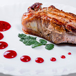 Roast meat with red sauce on a white plate thumbnail