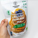 Hand holds vegan and organic Pancake baking mix with cinnamon and baobab powder by Superfood Bakery, is is gluten and dairy free