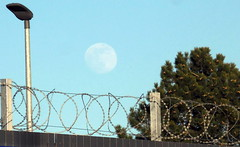 Full Moon rises through haze over razor wire fence (sms88aec) Tags: full moon rises through haze over barbed wire fence