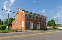 Frederick Nye Building — Tarlton, Ohio (Pythaglio) Tags: building structure historic tarlton ohio unitedstatesofamerica greekrevival italianate twostory brick chimneys commonbond integralgutter cornice brackets friezeboard centralpassage doublepile sidewalk street clouds wires cables vacant abandoned boarded 66windows stone lintels sills trabeateddoorway sidelights transom pilasters pickawaycounty fredericknye ca1850 pic6415