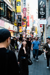 Crowd and korean signs in Myeongdong streets (kitsunekuma) Tags: seoul korea korean streetphotography streetfood street fujifilm fujinon fuji 35mm xpro1 xf xf35mmf2 beautiful woman signs busy crowd crowded myeongdong