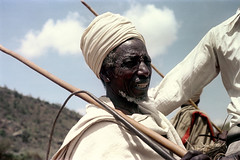 77-827 (ndpa / s. lundeen, archivist) Tags: nick dewolf color photograph photographbynickdewolf 1976 1970s film 35mm 77 reel77 africa northernafrica northeastafrica african ethiopia ethiopian centralethiopia southwesternethiopia southernethiopia people localpeople southerntribe tribespeople southerntribespeople man oldman face portrait sky clouds headcovering turban facialhair beard stick whip graybeard whitebeard