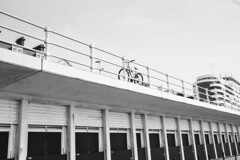 Seaside - Balancing Bke (julieloolibelle15) Tags: hastings 2019 may seaside shootfromthehip streets streetphotography england tradition documentary beach lifestyle summer towns people lines leadinglines highcontrast contrast bike bicycle architecture buildings abstract