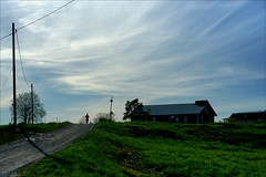 Running up that hill (*Kicki*) Tags: road barn sky clouds runner person people rural nature gottröra johannesberg johannesbergsslott sweden roslagen 50mm woman dirtroad farm