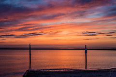 Mooring posts (wardkeijzer_107) Tags: sea sunset clouds red yellow orange tones bird water zeeland holland shadows composition netherlands beautiful nikon d7200 northsea