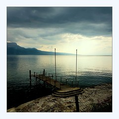 a little jetty (overthemoon) Tags: switzerland suisse schweiz svizzera romandie vaud bourgenlavaux lake léman lakegeneva water evening rainy sky jetty square frame mountains alps