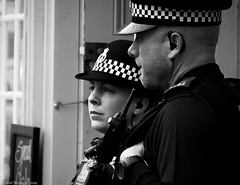 """Waiting for things to """"kick-off"""" (Neil. Moralee) Tags: brixhampirates neilmoralee police policewoman policeman officer law order man woman pair couple devon brixham uk hat band cheque cop cops street candid britain devonandcornwall constable constabulary waiting watching radio opperational ear earpiece male female risk black white bw blackandwhite bandw mono monochrome niel moralee nikon d7200 england"""
